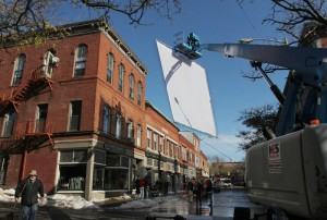 "A giant diffusion screen is hoisted from a cherry picker Wednesday during filming of the HBO miniseries ""Olive Kitteridge"" on Main Street in downtown Gloucester. (Mike Springer)"