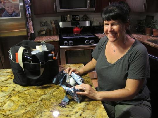 Honah Lee Milne searches through her costume kit. (Andrea Shea/WBUR)