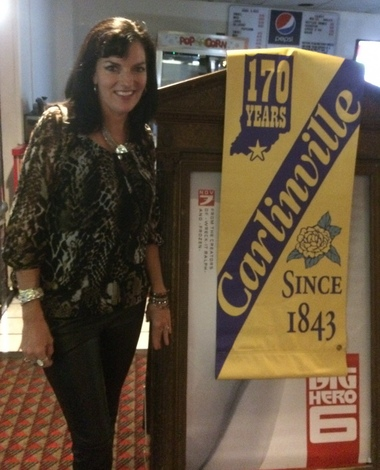 "Marie Schlosstein of Holyoke stands next to a Carlinville banner, a prop used in ""The Judge."" The film had a sneak preview in Greenfield on Wednesday, Oct. 8, 2014 (Ray Kelly 
