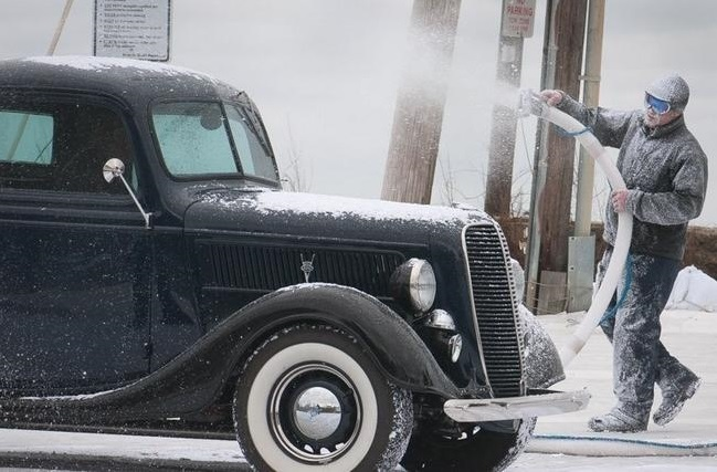 A production worker sprays artificial snow on a vintage car during the filming in Cohasset. (Courtesy Photo)