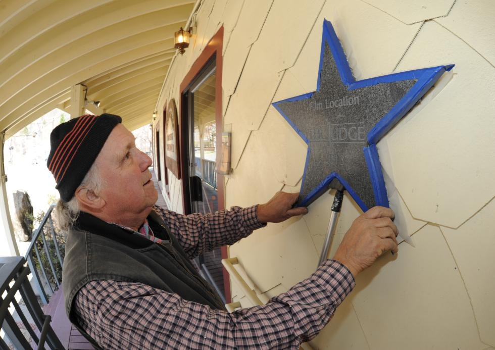 Jack Nelson of Carriage House Designs of Turners Falls mounts one of the 'movie stars' on the exterior of the Salmon Falls Market Place in Shelburne Falls where scenes from The Judge were filmed. (Recorder/Paul Franz)