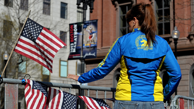 A woman in a Boston Marathon runners jacket reaches out to touch a barrier at a makeshift memorial blocks from the finish line on April 17, 2013 in Boston. (Photo credit should read STAN HONDA/AFP/Getty Images)