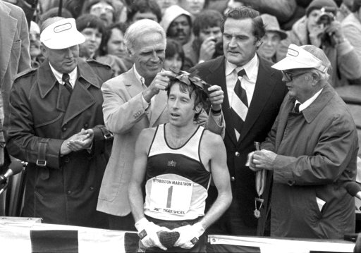 FILE - In this April 16, 1979 file photo, Bill Rodgers of Melrose, Mass., is crowned winner of the Boston Marathon by Mayor Kevin H. White, left, as Massachusetts Gov. Edward J. King, right, observes. A new film that captures much of the Boston Marathon's colorful history premieres Saturday, April 15, 2017, in conjunction with the 121st running of the race on Monday. (AP Photo, File)