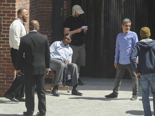 """(AMANDA SABGA/ Staff photo) Actor Danny Glover, seated, on the set of """"Proud Mary"""", an upcoming movie being filmed in Lawrence. In the blue Oxford shirt is film diretor Babak Najafi. Local actor Roger Dillingham is to the left of Glover in the white shirt."""
