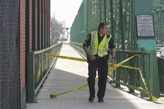 """(AMANDA SABGA/ Staff photo) Lawrence Police Sgt. Maurice Aguilar closes off foot traffic on one side of Duck Bridge as filming of the upcoming movie """"Proud Mary"""" gets underway."""